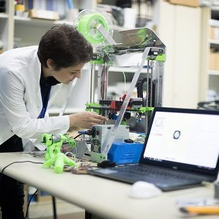 Mid adult woman repairing 3D printer in research lab